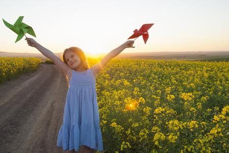 pinwheels: Girl playing with pinwheels outdoors LANG_EVOIMAGES
