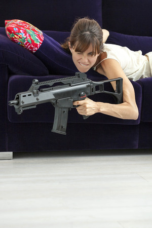aggressively: Woman shooting machine gun on sofa LANG_EVOIMAGES