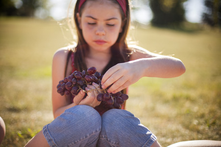morsels: Girl eating bunch of grapes in field