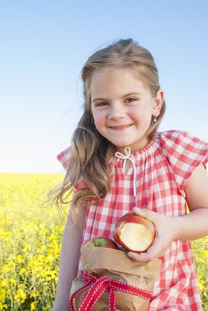checker: Girl eating sack of apples outdoors LANG_EVOIMAGES