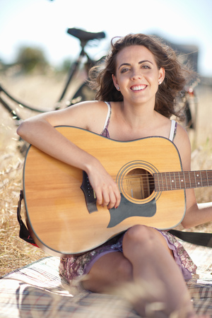 Woman playing guitar on picnic blanket LANG_EVOIMAGES
