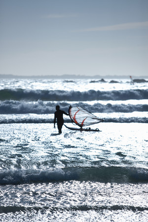 windsurfers: Man with wind sailing board in waves