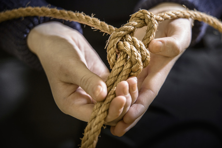 fastened: Student tying sheet bend knot in rope