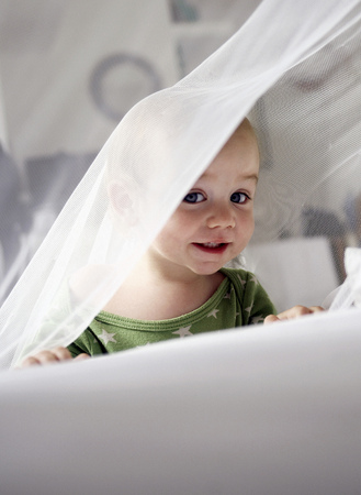Baby girl playing in sheer curtain