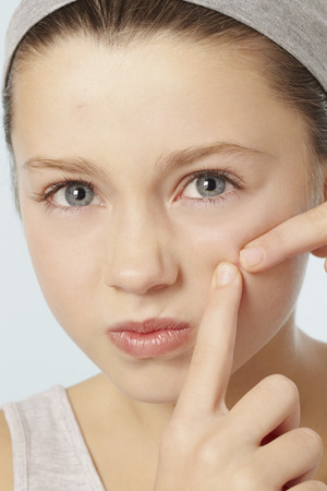 Girl squeezing spot on her face