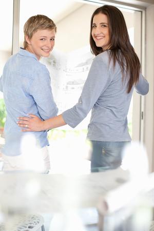 Women standing together by glass door