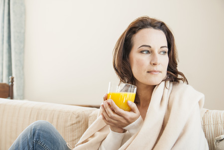 nourishing: Woman having cup of juice on sofa