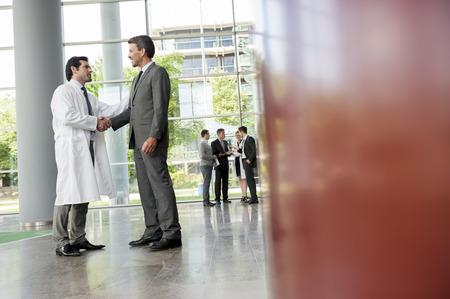 cerrando negocio: Hombre de negocios y doctor dándose la mano