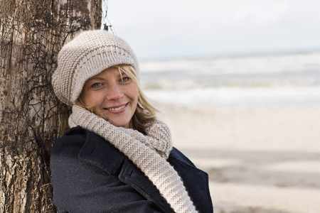 Smiling woman leaning against log