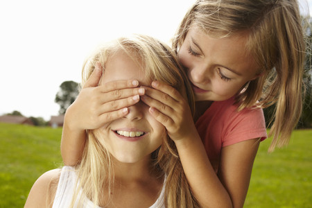 Smiling girl covering friends eyes