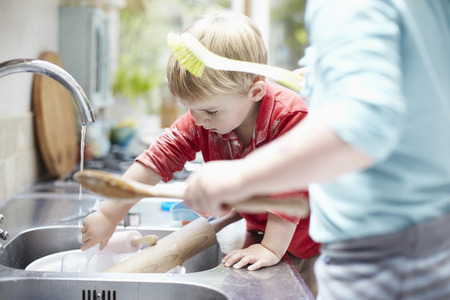 Children washing dishes together LANG_EVOIMAGES