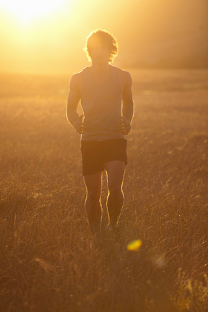 Man running in tall grass at sunset