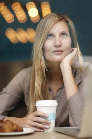 Woman having breakfast in coffee shop LANG_EVOIMAGES