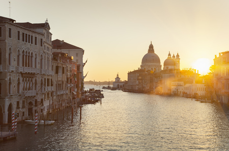 Sun setting over city buildings on canal LANG_EVOIMAGES