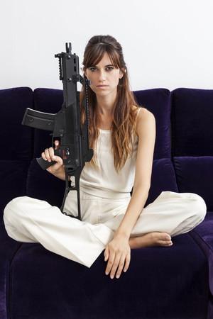 Woman holding machine gun on sofa LANG_EVOIMAGES