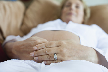 Pregnant woman relaxing on sofa