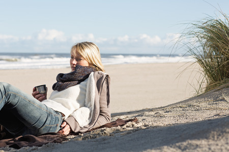 caffeine free: Woman drinking from thermos on beach