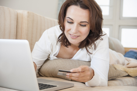 arrears: Woman shopping online on sofa LANG_EVOIMAGES