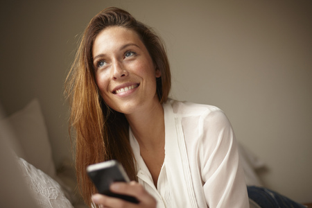 acknowledging: Woman using cell phone in bed