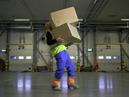 precarious: Worker carrying boxes in warehouse LANG_EVOIMAGES