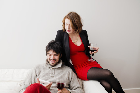 view of an elegant red couch: Couple drinking wine on sofa