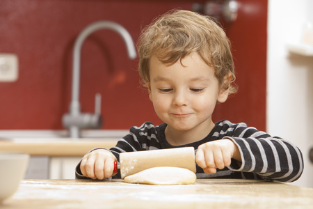 sway: Boy rolling pastry dough in kitchen LANG_EVOIMAGES