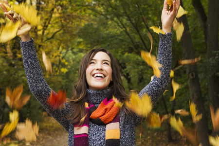 tosses: Woman playing in autumn leaves