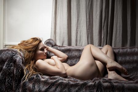 Nude woman laying on fur blanket