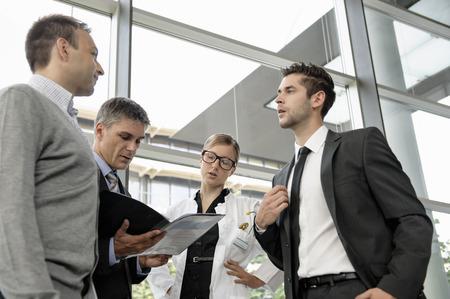 conferring: Doctor and businessmen talking LANG_EVOIMAGES