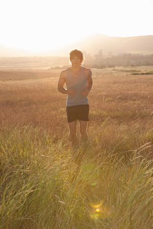 summers: Man jogging in tall grass
