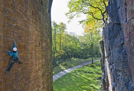 ascends: Rock climber scaling brick wall LANG_EVOIMAGES