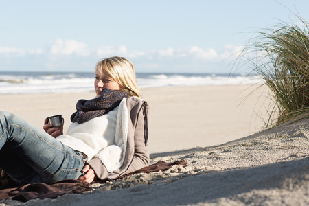 musing: Woman drinking from thermos on beach