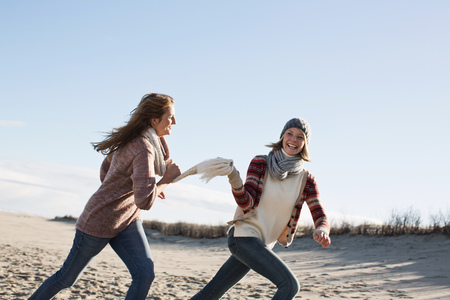 pursuing: Smiling women running on beach