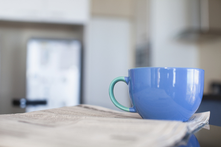 mornings: Cup of coffee and newspaper in kitchen
