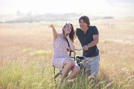 shared sharing: Couple playing on bicycle in tall grass