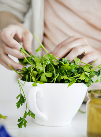 nourishing: Woman putting fresh herbs in bowl