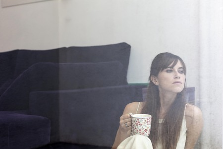 somber: Woman having cup of coffee at window