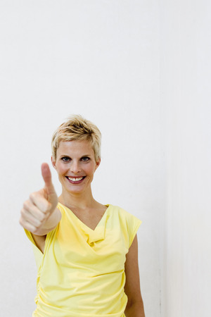agrees: Smiling woman giving 'thumbs up