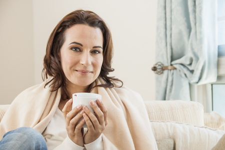 divan: Woman having cup of coffee on sofa
