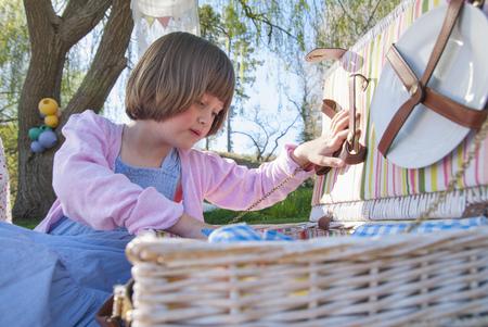Girl unpacking picnic basket outdoors LANG_EVOIMAGES