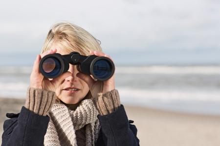 Woman using binoculars on beach LANG_EVOIMAGES