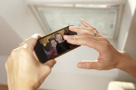 通信: Woman examining picture on cell phone