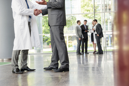 Businessman and doctor shaking hands LANG_EVOIMAGES