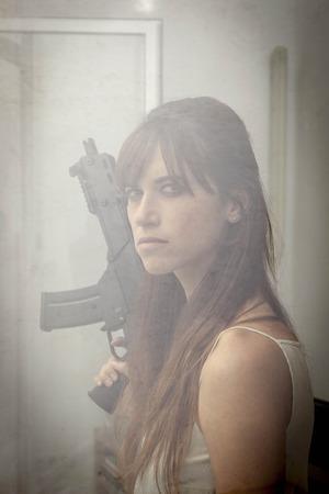 Woman holding machine gun at window LANG_EVOIMAGES