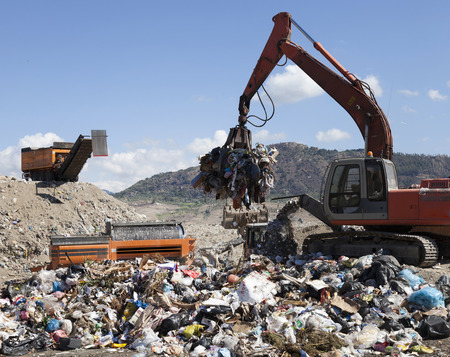 industrialization: Machinery grabbing waste in landfill