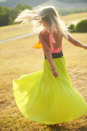 Girl spinning in skirt in field LANG_EVOIMAGES