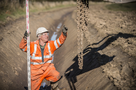 Worker directing digger in surface mine