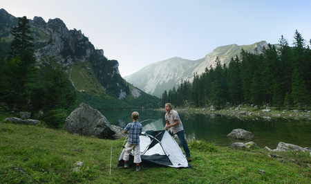 shorelines: Father and son pitching tent together LANG_EVOIMAGES