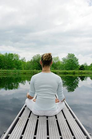 Man meditating on wooden pier