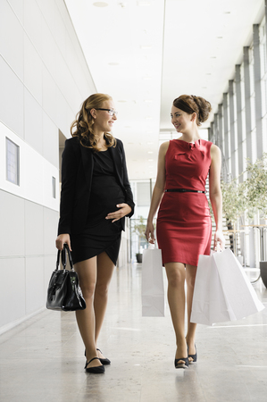 shopping buddies: Businesswomen talking in lobby LANG_EVOIMAGES